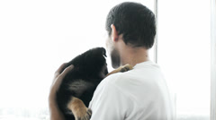 Young man holding a German Shepherd puppy in her arms and looking out the window Stock Footage