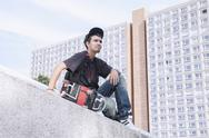 Stock Photo of Thoughtful young man with skateboard sitting against building