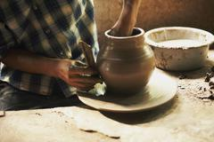 Cropped image of male potter moulding clay in workshop Stock Photos
