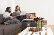 Stock Photo of Mid adult couple using laptop on sofa in living room
