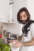 Portrait of man cooking in domestic kitchen Stock Photos