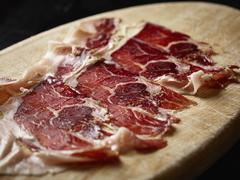 Slices of meat on cutting board over black background Stock Photos