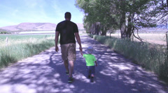Father & son walking away from camera down lane-HD-P-4144 Stock Footage