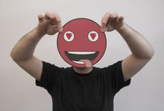 Man holding a romantic emoticon face in front of his face Stock Photos