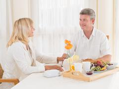loving mature couple enjoying a healthy breakfast smiling at each other - stock photo