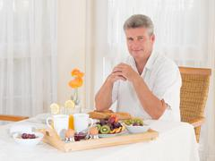 senior mature man sitting down to a healthy breakfast looking at camera - stock photo
