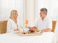 happily mature senior married couple enjoy a healthy breakfast holding hands - stock photo