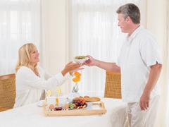 mature senior husband serving his wife healthy breakfast - stock photo