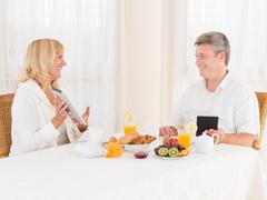 Happy mature healthy couple using tablets and ebook ereaders at breakfast Stock Photos