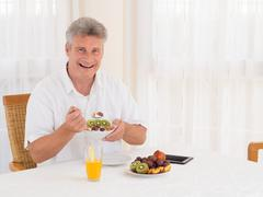 laughing mature man eating a healthy cereal breakfast - stock photo