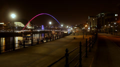 A time lapse of the millenium bridge and people in a city at night - stock footage
