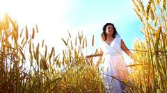 Beautiful, young woman walking across the wheat field Stock Footage