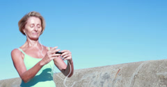 Fit senior woman pausing on her run to change her music - stock footage