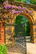 Stock Photo of Garden Stone Arched Gateway Surrounded by Flowers