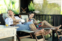 Couple talking on cellphone, relaxing on terrace in tropical place NTSC Stock Footage