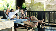 Couple chatting on tablet, relaxing on terrace in tropical place HD Stock Footage
