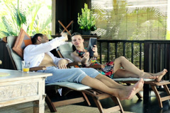 Couple chatting on tablet, relaxing on terrace in tropical place NTSC Stock Footage