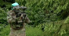 A man with camouflage outfit is playing a paintball Stock Footage