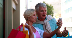 Happy couple on day out shopping looking at smartphone Stock Footage