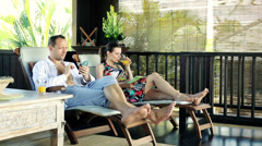 Couple with smartphone and book relaxing on terrace in tropical place HD Stock Footage