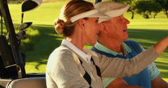 Happy couple sitting in kart looking around the golf course - stock footage