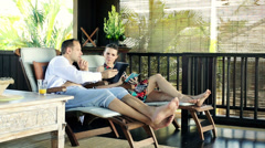 Couple with smartphone and with tablet on terrace in tropical place HD Stock Footage