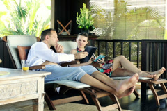Couple with smartphone and with tablet on terrace in tropical place NTSC Stock Footage