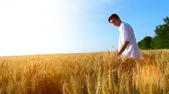 Young man standing in the wheat field Stock Footage