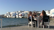 Stock Video Footage of Four young girls sitting in front of little venice in Mykonos Island in Greece