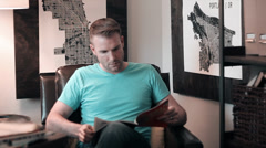 Man Casually Reading Magazine in Leather Chair Stock Footage