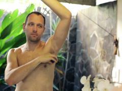 Man applying antiperspirant on his armpit in the bathroom NTSC Stock Footage