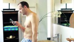 Man in underpants texting on smartphone in the bathroom HD Stock Footage