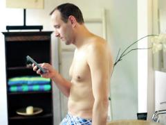 Man in underpants texting on smartphone in the bathroom NTSC Stock Footage
