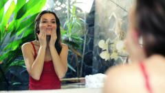 Pretty woman applying cream on her face in front of the mirror HD - stock footage