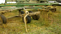 Big harvesting machine is turning above dry grass, truck with hay maker - stock footage