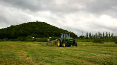 Tractor with hay maker working on the meadow. Haymaking in the countryside Stock Footage