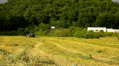 tractor harvesting grass, truck with hay maker working on meadow in farmland. - stock footage