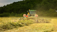 Tractor harvesting grass, truck with hay maker working on the meadow in farmland Stock Footage