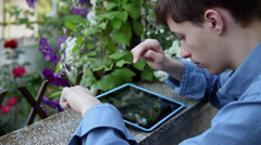 Teenage boy playing games on a tablet computer, leisure time, home garden - stock footage