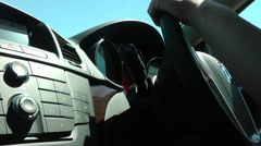 Woman using steering wheel in a moving car on a sunny day Stock Footage