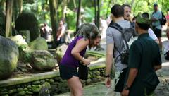 Tourists sightseeing ancient Ubud monkey forest in Bali, HD - stock footage