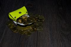 light green pocket has gold coin gush on wood - stock photo