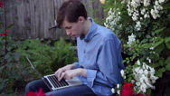 Stock Video Footage of Teenage boy using a laptop in the romantic rose garden