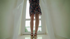 Beautiful woman with bare feet standing at the window - stock footage