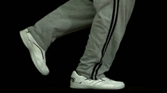 Legs in tracksuit running against black background - stock footage