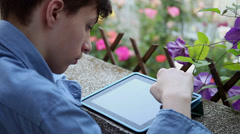 Teenage boy with tablet computer in the garden, young male student - stock footage