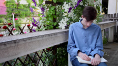 Teenager writing in his notebook on terrace in summer Stock Footage