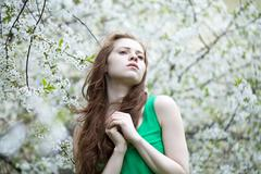 beautiful young girl standing near blooming trees in spring garden - stock photo