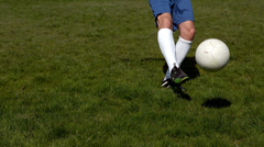 Football player kicking the ball on grass Stock Footage