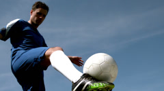 Football player kicking the ball up under blue sky Stock Footage